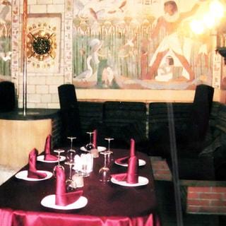 На фото: помещение ресторана, сервированный стол, стены декорированы камнем, украшены рисунками