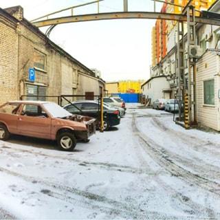 На фото: часть внутренней территории между двумя зданиями, припаркованные автомобили