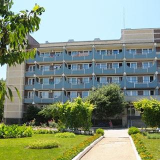 На фото: 5-этажное панельное здание с балконами, большое входное крыльцо со ступенями, благоустроенная прилегающая территория, асфальтированные дорожки, газоны, садовые кусты и деревья