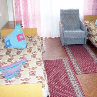На фото: комната с окном, две кровати, прикроватная тумбочка, кресло