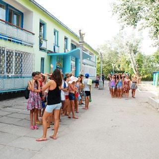 На фото: двухэтажный жилой корпус, перед домом - дети с вожатыми