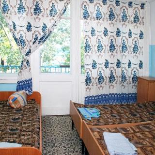 На фото: комната с окном и выходом на балкон, три кровати, прикроватная тумбочка