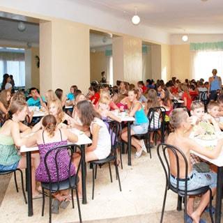 На фото: обеденный зал во время приема пищи детьми, столы на 4 человека