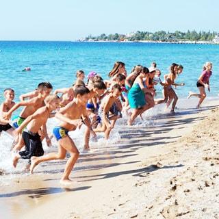 На фото: море, песчаный пляж, выбегающие из моря после купания дети