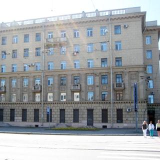 Фото сделано с Благодатной улицы. На фото: часть фасада кирпичного дома сталинского типа с элементами декора и балконами, тротуар и проезжая часть улицы.