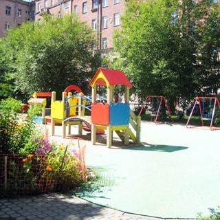 На фото: часть светлого благоустроенного зеленого двора с детской площадкой и цветочными клумбами.