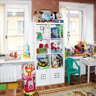 На фото: комната, два окна, на окнах - стеклопакеты, две батареи центрального отопления, детская мебель, игрушки, полы - линолеум