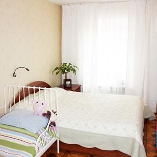 На фото: комната, одно окно, двуспальная кровать, детская кровать, тумбочка, полы - линолеум