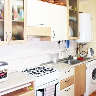 На фото: кухня, газовая плита, столы-тумбы, мойка со смесителем, стиральная машина, навесные шкафы, бойлер