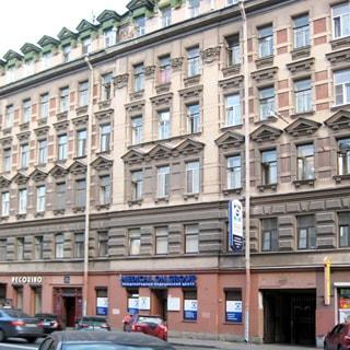 На фото: часть фасада жилого 6-этажного дома, старый фонд, лепнина, элементы декора, в первых этажах - магазины, офисы, кафе, парадная, арка во двор с воротами