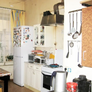 На фото: кухня, газовая плита, вытяжка, стол-тумба, навесной шкаф, холодильник, кухонная техника, окно