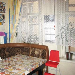 На фото: кухня, мягкий кухонный уголок, детский стул, два окна, в окне - стена дома напротив