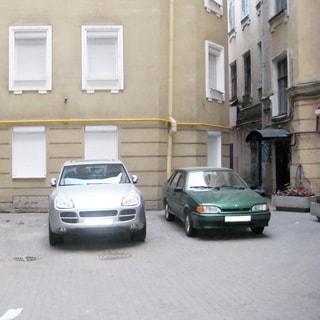 На фото: двор - колодец, с возможностью парковки, вымощен тратуарной плиткой, установлены тумбы с цветами