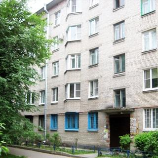 На фото: часть фасада 5-этажного кирпичного дома с эркерами, парадная, участок придомовой территории с газоном и тротуаром