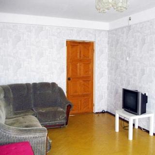 На фото: комната, полы - паркет, стены оклеены обоями, диван, столик с телевизором
