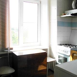 На фото: кухня, окно со стеклопакетом, плита - газовая, над плитой - вытяжка, кухонный раскладной стол-книжка, стул, табурет, стены облицованы плиткой