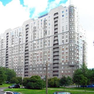 На фото: фасад 18-этажного дома с эркерами, отделка - кирпич, камень, перед домом проезжая часть, разделенная широкой аллеей с газоном и деревьями