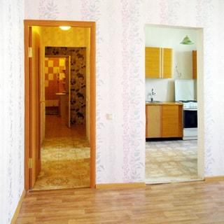 На фото: часть комнаты, выход в коридор с дверью, выход в кухню - проем без дверной коробки, стены - обои, полы - линолеум, на заднем плане - коридор, санузел, кухня