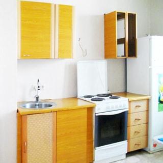 На фото: часть кухни, столы-тумбы и навесные шкафы, электрическая кухонная плита с духовкой, металлическая мойка со смесителем, двухкамерный холодильник