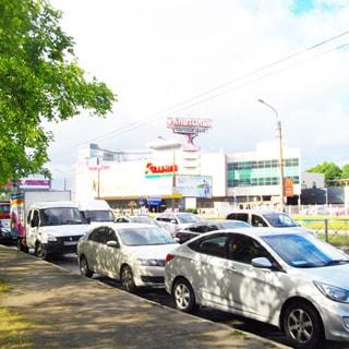 На фото: проезжая часть улицы, припаркованные и едущие автомобили, на заднем плане большой торговый центр под названием Капитолий