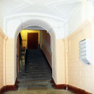 На фото: чистая светлая парадная, лестница на первый этаж, на стене - почтовые ящики.