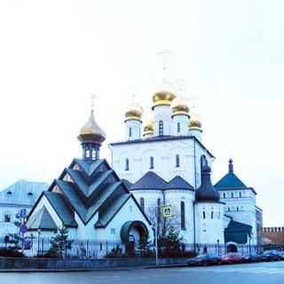 На фото: православный собор с золотыми куполами на огороженном участке, прилегающая территория - улица с припаркованными автомобилями, на дальнем плане справа - кирпичная стена, похожая на кремлевскую.
