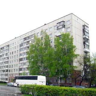 На фото: часть фасада панельного 9-этажного дома с балконами и лоджиями, прилегающая территория - улица с припаркованными автомобилями, на придомой территории - газон, деревья, кусты.