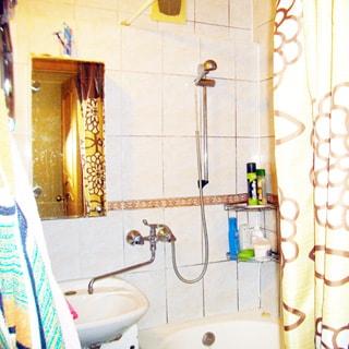 На фото: часть ванной, керамическая раковина, над раковиной - зеркало, справа - ванна, смеситель общий для раковины и ванны, стены - плитка.
