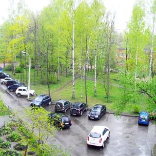 На фото: вид из окна в большой благоустроенный двор, газоны, клумбы, деревья, возможность для парковки.