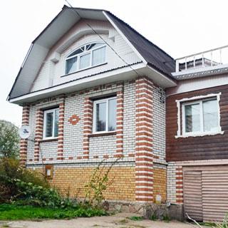 На фото: одноэтажный загородный дом с деревянной пристройкой, с подвалом и мансардой, облицован кирпичом и сайдингом, окна - стеклопакеты