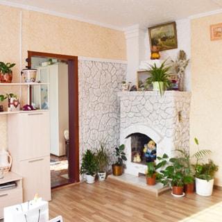 На фото: внутреннее помещение - комната с камином, полы - ламинат, стены - обои, современная мебель светлых тонов, цветы - в горшках расставлены у камина