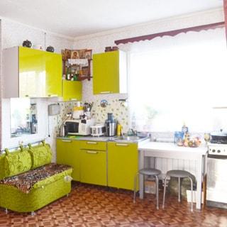 На фото: внутреннее помещение - кухня с большим окном, мягкий диванчик, кухонный гарнитур с навесными шкафами и столами-тумбами, мойка, кухонный стол, газовая плита, полы - линолеум