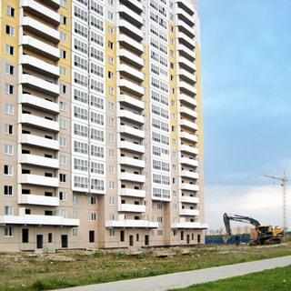 На фото: часть фасада 19-этажного панельного дома с застекленными лоджиями, три парадные, участок придомовой территории с газоном и тротуаром, на заднем плане справа - экскаватор и строительный кран