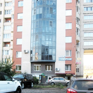На фото: часть фасада многоэтажного дома, фасад кирпичный, лоджии, в цокольном этаже - универсам, перед домом газон, припаркованные автомобили