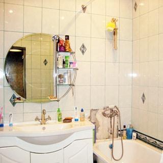 На фото: ванная комната, широкая керамическая раковина со смесителем, зеркало с полкой, ванная со смесителем, стены облицованы светлой керамической плиткой