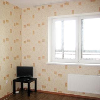 На фото: чистая, светлая комната, одно большое окно, установлен стеклопакет, батарея центрального отопления, полы - линолеум, стены оклеены обоями, в углу - столик, на столике - телевизор