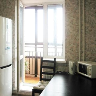 На фото: часть кухни, окно с балконной дверью, дверь на балкон открыта, балкон застеклен, слева от окна - двухкамерный холодильник, под окном - батарея центрального отопления, справа от окна - обеденный стол, на столе - электрический чайник и микроволновая печь, у стола - стул