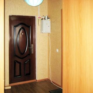 На фото: прихожая, металлическая выходная дверь, справа от двери - ящик электрощитка, полы - линолеум, стены оклеены обоями