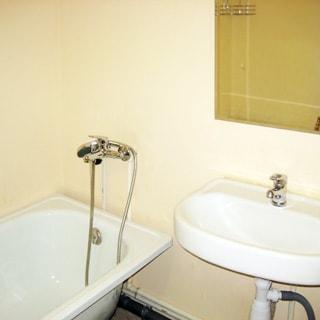 На фото: часть санузла, ванная со смесителем, керамическая раковина со смесителем, над раковиной - зеркало, стены окрашены