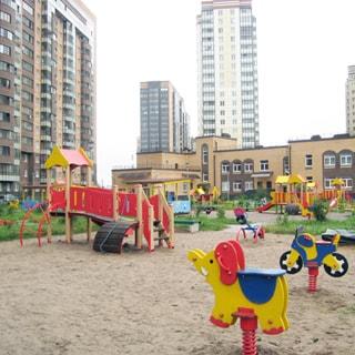 На фото: часть дворовой территории, большая оборудованная детская площадка, примыкающая к детскому саду, вокруг детской площадки - газон