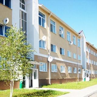 На фото: фасад трехэтажного многоквартирного дома, фасад оштукатурен, окна квартир - стеклопакеты, вход в подъезд и лестничные пролеты - панорамное остекление, перед домом - газон, тротуар