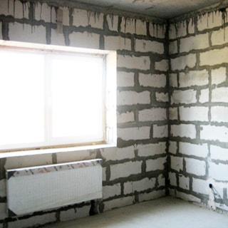 На фото: часть комнаты с окном, установлен стеклопакет, под окном - радиатор отопления, стены - пеноблоки без отделки, пол - цементно-песчаная стяжка
