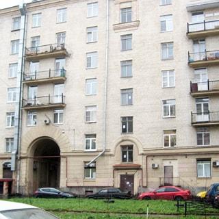 Фото сделано со двора. На фото: часть фасада серого кирпичного дома с элементами декора, балконами, въездной аркой и благоустроенный двор с возможностью парковки.