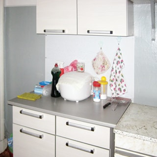 На фото: часть кухни, кухонный стол-тумба, скороварка, навесной шкаф.