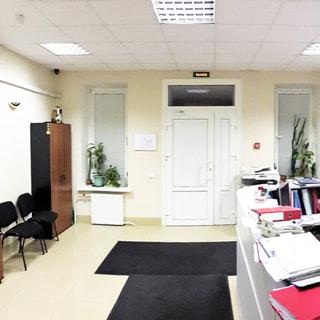 На фото: часть помещения приемной, входная дверь, справа и слева от двери по одному окну, по левой стене шкаф для одежды, стулья для посетителей, по правой стене - стойка администратора, полы - плитка, потолки - подвесные