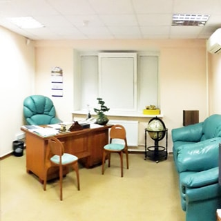 На фото: часть помещения кабинета руководителя, окно, у окна слева письменный стол с офисным креслом, под окном радиатор отопления, справа у стены два мягких кресла, на стене - кондиционер, потолки - подвесные