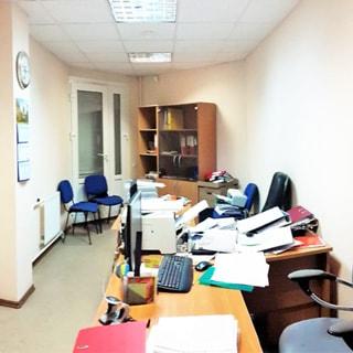 На фото: часть офисного помещения, балконная дверь, офисная мебель (столы, кресла, стулья, шкафы), слева на стене радиатор отопления, потолки - подвесные