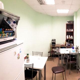 На фото: помещение столовой для персонала, слева - холодильник, на холодильнике - микроволновая печь, два небольших стола для приема пищи, шкаф и стол для посуды и столовых принадлежностей, стулья, потолки - подвесные