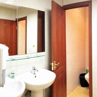 На фото: часть помещения санузла, два туалета, два умывальника, перед умывальниками слева на стене - зеркало