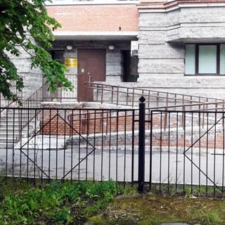На фото: часть фасада кирпичного здания, первый этаж отделан декоративным камнем, вход в помещение оборудован лестницей, пандусом для маломобильных групп населения, металлической дверью, вывеской, перед зданием - асфальтированный дворовый проезд
